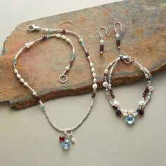 EMBERS & ICE COLLECTION - The passionate glow of red garnet and the frosty cool of sterling silver, apatite and pearls join a glittering faceted blue topaz in handcrafted sterling, pearl and gemstone jewelry that makes the event.