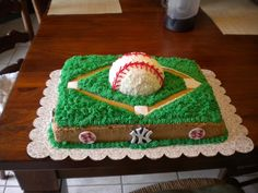 "Entire cake covered in buttercream. ""Outfield"" was made with peanut butter icing. Filling was vanilla pudding & fresh strawberries. Baseball was star-tipped & then piped. Logos were made out of fondant."