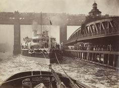 """HMS Victoria passing swing bridge while en route from Armstrong Shipyard at Elswick"". Newcastle-upon-Tyne. c. 1890."