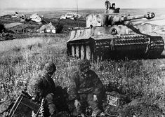 A Waffen SS Tiger 1 during the battle of Kursk, advancing from a Russian hamlet and driving by a group of Panzergrenadiers manning a machine-gun post.