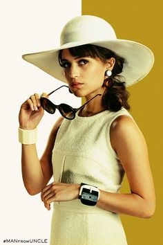 Gaby Teller (played by Alicia Vikander) is our new favorite style icon. Classic sunglasses, a sun hat, cuff bracelets, and mod earrings complete her look. | The Man from U.N.C.L.E.