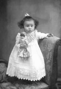 Victorian portrait of a little girl with her doll, wearing a beautiful dress.
