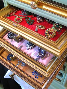 What a great idea for jewelry holder. Old picture frames painted gold, or really any way you would like, pretty fabric and a storage box to slide them into.