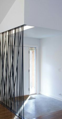 Black wired wall, creating a barrier/hallway between the front door and rest of home