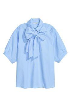 Bluzka z wiązaniem: Bluzka z bawełnianej tkaniny z krótkim bufiastym rękawem. Kołnierzyk z szerokim wiązaniem i zapięcie u góry.