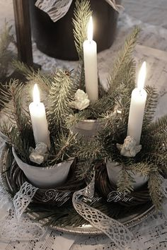 white christmas candles in greenery filled pots