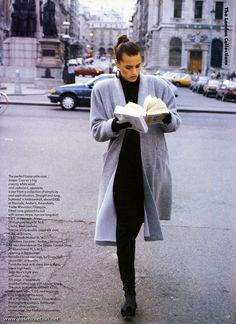 "Yasmin Le Bon reading books in street in ""New Day at the London Collections"" for UK Vogue, August 1986. Photographer: Peter Lindbergh.  ""Jean Muir's light grey soft wool wrap, a beautifully unembellished look with tubular black. The coat, buttonless,..."