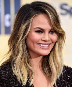 The best celebrity bangs for round faces: A long swooping fringe and deep side part create flattering angles on a round round face like that of Chrissy Teigen.