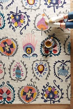 Crewelwork Jovana Rug. This vibrant floor covering features intricate embroidery that calls to mind ancient tapestry motifs. The crewel technique is an embroidery method synonymous with wool rugs and stitched designs.