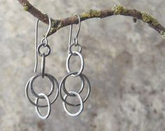 Fluid and tactile, these earrings are a lesson in elegant simplicity! I've torch fused varying gauges of fine silver wire into interlocking rings,