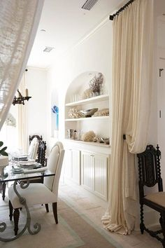 linen draperies create visual interest and seperation between rooms in an open concept home  (pretty beach house dining)