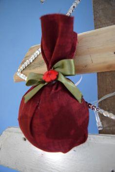 Enfeite de Natal: Meia bolinha de isopor envolvida com tecido amarrada com fita.