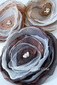 Organza Flowers Tutorial   Cut circular shapes and/or petals out of organza preferably synthetic materials so you can burn the edges up Sew the petals altogether in the very centre, adding beads, crystals, pearls, buttons, whatever