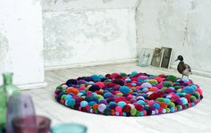 carpet  - i think this is  collection of pom poms make from wool different sizes stitched together to make a carpet. very effective and great for using up wool!