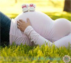 Jolie photo de grossesse : ventre rond et chaussures de bébé