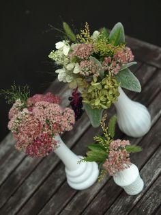 Wildflower arrangements in milk glass bud vases. Pink sedum, hydrangea, grass seed pods and lamb's ears greenery.  www.rosehipsocial.com