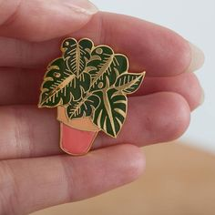 The perfect pin for an plant lover. This Cheese-plant pin makes a great gift for someone that who loves their houseplants. A beautiful plant pin. A hard enamel pin, based on a watercolour illustration of a Monstera potted plant by Illustrator Eleanor Longhurst. Pop it on your collar, bag or coat to jazz up your outfit! Presented on a backing card, this pin measures 3 cm across, and is made from shiny gold metal with green enamel leaves and a pink enamel plant pot. This pin has a butterfly…