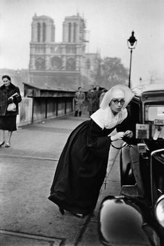 Bonne soeur accoudée à un taxi, on distingue la cathédrale de Notre-Dame de Paris en arrière plan - 1963 © Copyright Marc RIBOUD