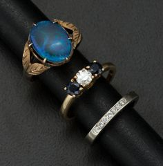 A set of three rings, featuring sapphires and diamonds set in a variety of metals.