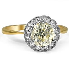 This stunning Edwardian engagement ring features a beautiful fancy yellow center diamond surrounded by a floral halo of white diamonds in milgrained frames.