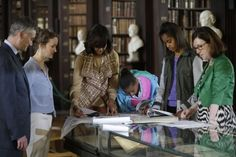 US first lady Michelle Obama, center, with her daughters Sasha, and Malia, second from the right, look through archives documenting the Obama's Irish Ancestry during their visit to the Old Library at Trinity College, in Dublin, Ireland, Monday, June 17, 2013. The first lady and her daughters were given a presentation on their own family genealogy and connection to Ireland. (AP)