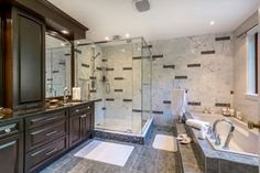 A bathroom with a variety of style, this space incorporates different sizes and styles of tile on the walls and floor, along with light granite on the walls, and rich stained wood for the cabinetry. The tub and shower are both adequately spacious.