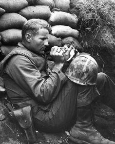 "A US Marine feeds an orphan kitten found after a heavy mortar barrage near ""Bunker Hill"" during the Korean War. (Photo by Sgt Martin"