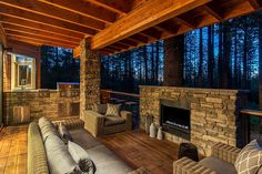 Stone and wood outdoor deck on the cabin with barbecue zone and fireplace [Design: Jenifer Giudice]
