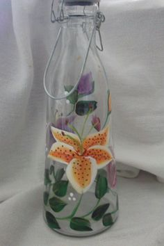 Hand painted wine carafe. Painted with beautiful colorful lilies of orange, purple and pink. Makes for a lovely display to your entertaining.