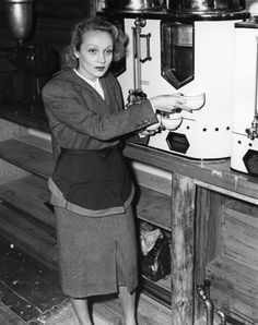 Marlene Dietrich, wearing the official apron, draws a couple of cups of coffee in the snack bar at the Hollywood Canteen where she is a hostess. photo dated - October 5, 1942