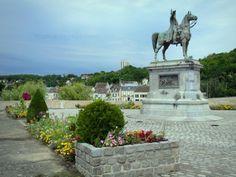 Montereau-Fault-Yonne: Statue équestre de Napoléon Ier au confluent de l'Yonne et de la Seine, parterres de fleurs, et façades de maisons du quai de Seine en arrière-plan - France-Voyage.com