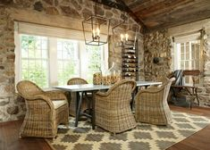 The sleek dining table and wicker chairs in this dining room are different styles that work well together. Large lanterns bring great light to the dining space without feeling oversized, and an Aztec-style rug echoes the neutral tones in the stone cottage but adds a funky, modern feel to the space.