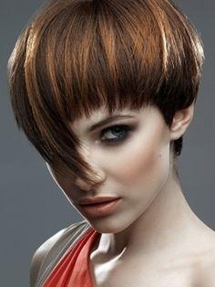 Inspirée de la coupe au bol, cette coiffure est très jolie. Tout se joue au niveau de la frange, laquelle est plutôt courte d'un côté, mais très longue de l'autre, descendant sur le nez de la jeune femme. Pour éclaircir sa coloration brune, le coiffeur a appliqué des mèches noisette dans ses cheveux.