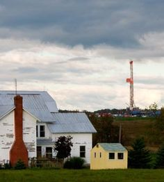 A gas drilling well pad sits on a hill behind a farm house in Faridale, Pennsylvania, October 2, 2011