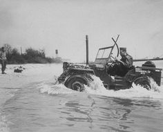 1/4-ton 4x4 truck (jeep) coming up out of water to beach. This vehicle has a record of staying under water for 71 minutes and its depth of submersion is limited only by the length of the exhaust pipe and the deep sea diving equipment of the driver. Between Coal Pier and Pier X, Hampton Roads Port of Embarkation, Newport News, VA, 22 April 1943.