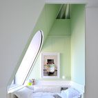 This four-level penthouse apartment in New York has some quieter moments (to contrast with the multistory reflective slide snaking throughout). Designed by architect David Hotson_Architect with interiors by Ghislaine Viñas, this top-floor bedroom is a minty moment of repose. Set into the dormer at the opposite side of the bedroom, the alcove bed occupies a wedge of space extending up to the attic-level oculus window. Photo: David Hotson.