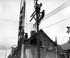 Deux soldats américains du Signal Corps sont montés en haut dun poteau et réparent les lignes téléphoniques de la ville. Au croisement de la rue Holgate et de la voie ferrée Paris-Cherbourg, voir la barrière verticale du passage à niveau à gauche.