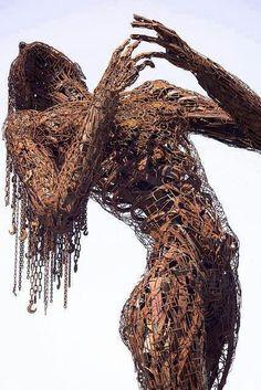 Sculpture, woman, chains, metal, steel, brown, human figure.