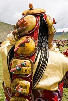 Tibet | Lovely Khampa Finery ~ Nagchu horse racing festival in 2009. Girl's remarkable ceremonial costume included a headpiece of enormous amber beads and beautiful robes and necklaces of dzi and coral. | © BetterWorld2010