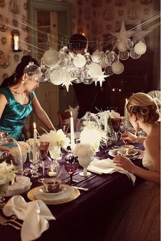love the ornaments above the table, deep table cloth and taper candles. so beautiful and has a vintage feel