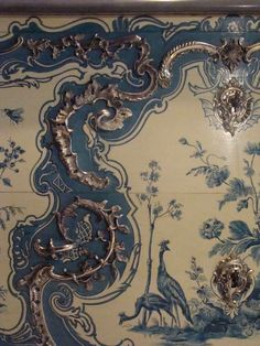Matthieu Criaerd (1689-1787)  Commodedetail  1742  Blue Room, Château de Choisy, France  Commode coated with blue and white vernis Martin, representing exotic birds and plants, inspired by blue and white Chinese porcelain motifs. The silvered bronze decoration consists of a series of scrolls, and a wavy border pierced with ovals, scrolls, and foliage. The blue and white furniture in the Blue Room reflected Madame de Mailly taste for oriental art. This type of decoration became very…