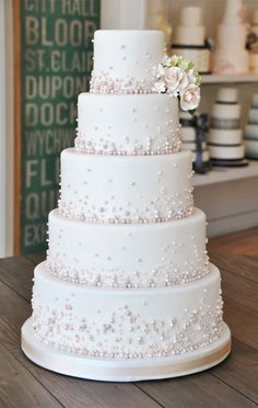 One (possibly 2 small) layered cake with these rose colored candy beads. Simple, yet elegant.