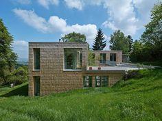 Venez visiter une maison construite sur un terrain en pente.