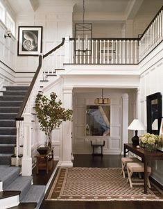 White paneled walls, dark steps and floors, that bottom step that continues along the wall...I love everything about this foyer.