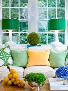 white sofa emerald green lamps and pillows