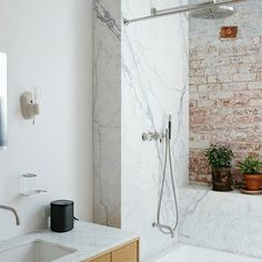Scandinavian designed master bathroom with exposed brick, marble, an amazing rain shower head in the incredible shower. Wall hung vanity, wall mounted faucet and minimalist mirror hung above. Modern Bathrooms Interior, Gravity Home, Wall Hung Vanity, Manhattan Loft, Nyc Loft, Scandinavian Home, Exposed Brick, Sonos, Bathroom Decor