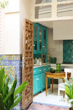 The kitchen that opens to the courtyard features white marble floors, green handmade tiles, and custom-made cabinetry painted in green and white.