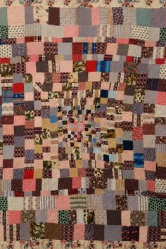 Welsh patchwork quilt made from multicoloured printed cotton squares. The filling is probably an older quilt. Made by Esther David of Llanfabon. Mid to late 19th century.