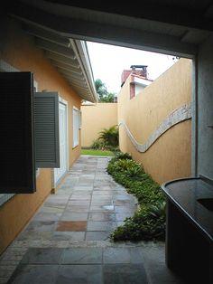 Painel em pedra portuguesa no muro, como uma onda, com desenho de Liliane Mancebo. No piso, o desenho inspira o formata do pequeno jardim que acompanha o mesmo movimento. Projeto realizado para uma casa de praia no litoral do RS.