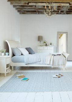 We brushed a lovely off-white heritage paint onto the grainy wood of this hand-carved Lauren sleigh style bed. With a whiff of the Scandinavian about it, we love this neutral white bedroom.
